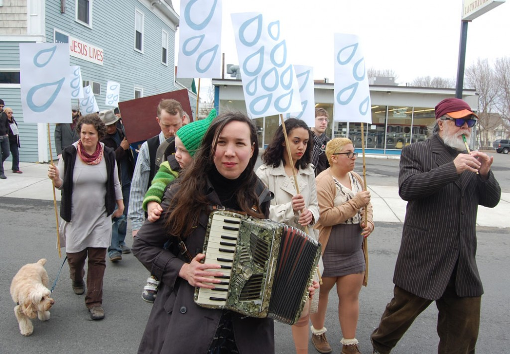 Kari Percival, with son Ulysses on her back, plays accordion. Mark Dannenhauer plays flute.