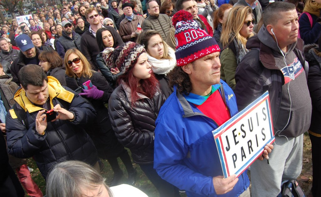 """Boston Marathon Bombing hero Carlos Arredondo stands at the front of the crowd at the bandstand holding a sign """"Je Suis Paris"""" (I Am Paris). (Greg Cook)"""