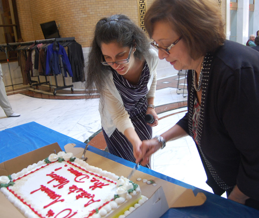 Kathleen Bitetti (left), the organizer of the annual Artists Under the Dome, cuts a cake to mark the annual event's 10th anniversary at the Massachusetts State House, Nov. 2, 2016. (Greg Cook)