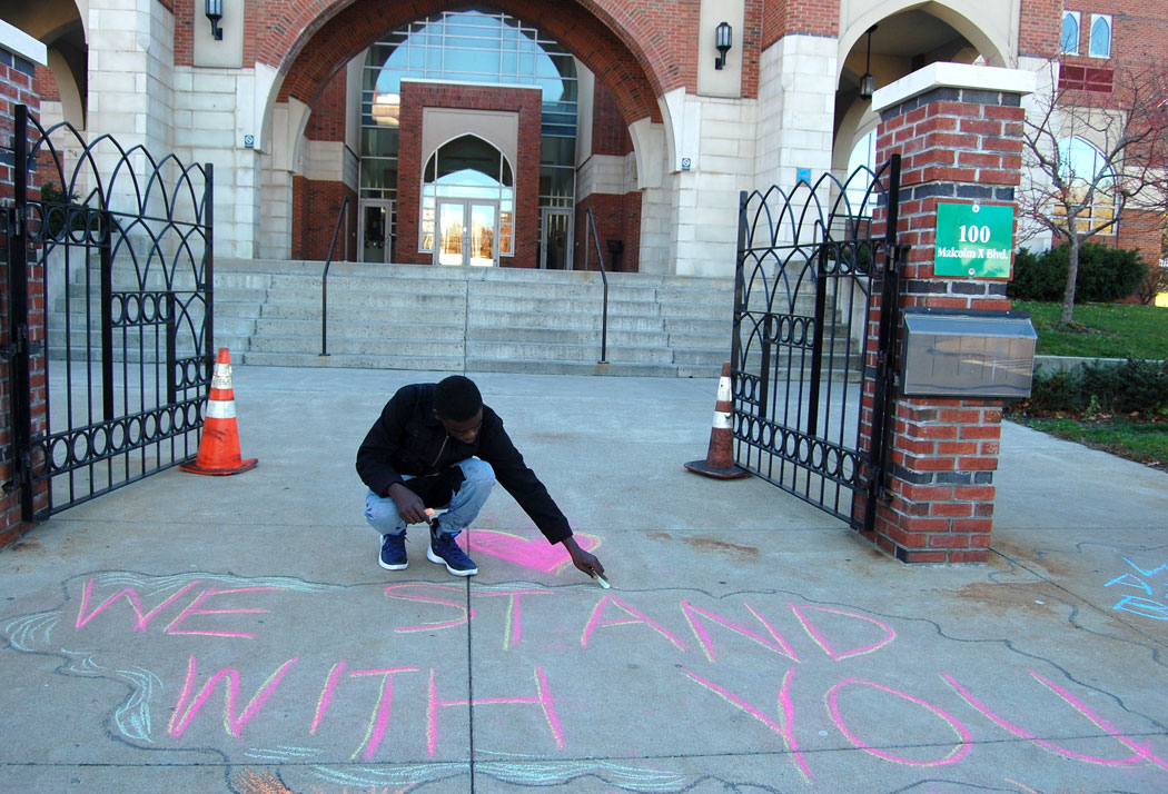 """We stand with you."" MassMovement activists write on the sidewalk outside the Islamic Society of Boston Cultural Center on Malcolm X Boulevard, Boston, Nov. 18, 2016. (Greg Cook)"