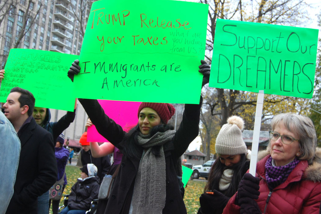 """""""Trump release your taxes. What are you hiding from US?? Immigrants are America."""" """"Support our dreamers."""" At """"Love Trumps Hate"""" rally at Boston Common, Nov. 20, 2016. (Greg Cook)"""