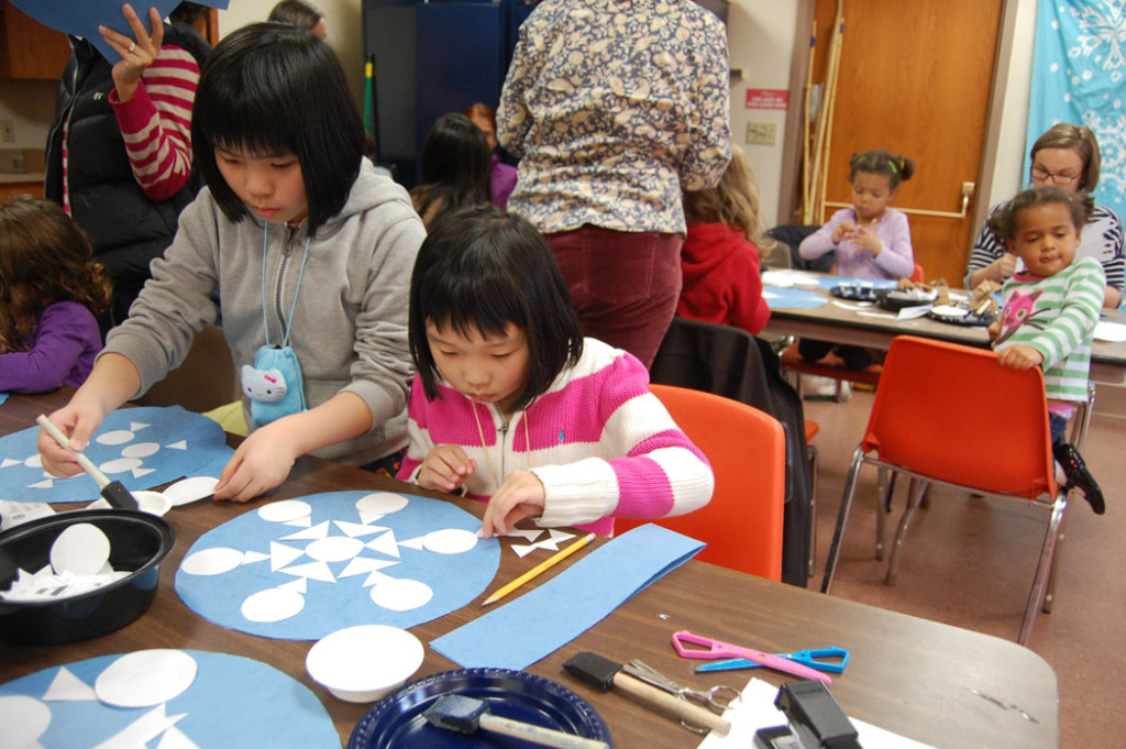 """Making snowflake hat at the Malden Public Library for the """"Let It Snow! Santas Against Global Warming!"""" parade group, Saturday, Nov. 19, 2016. (Greg Cook)"""