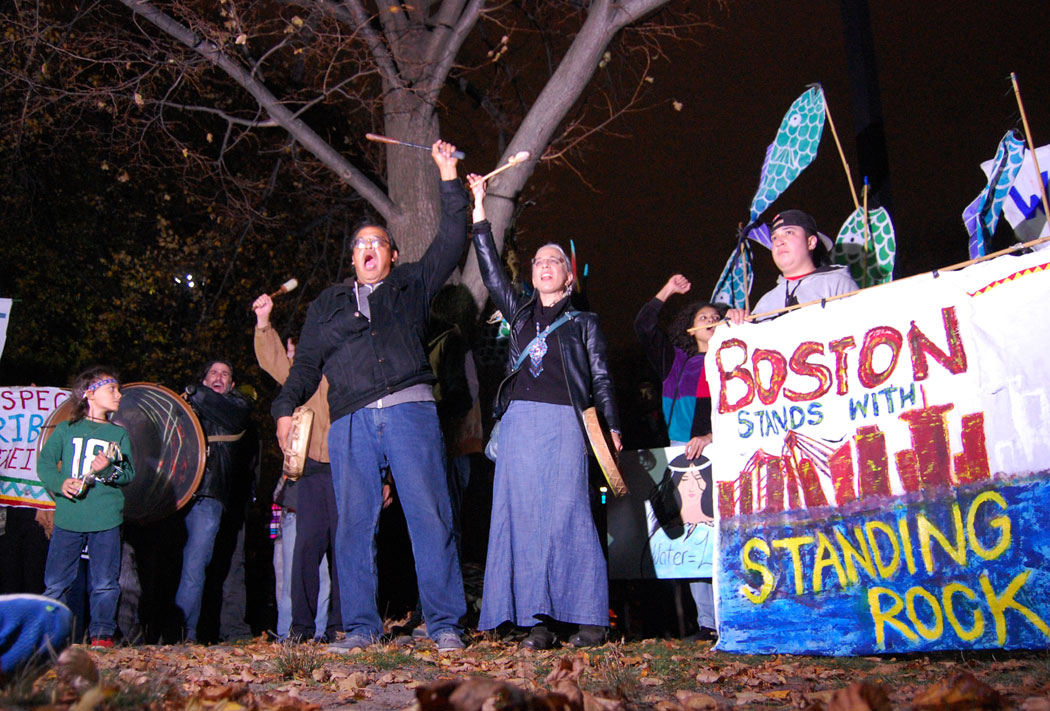 """""""Water is life,"""" Karan Doczi (center right) shouted when the """"Boston Stands with Standing Rock"""" group formed a circle near the Charles River. (Greg Cook)"""