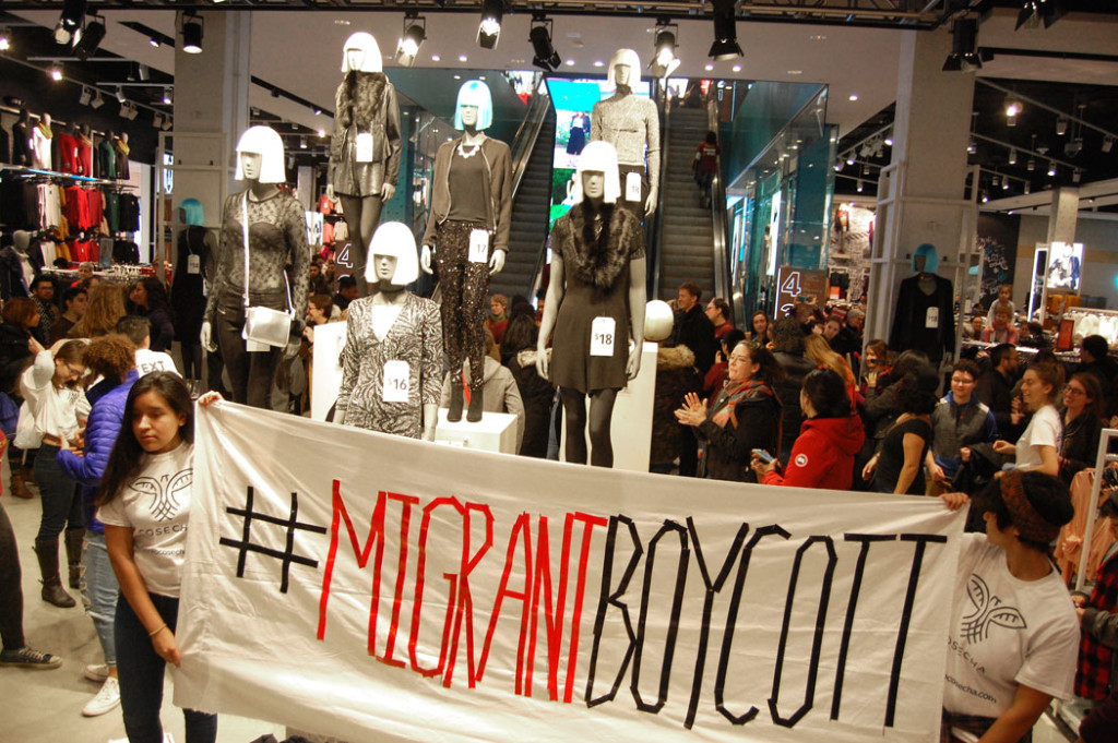 "Immigrant rights protesters unfurl a banner reading ""#MigrantBoycott"" inside the lobby of Primark. (Greg Cook)"