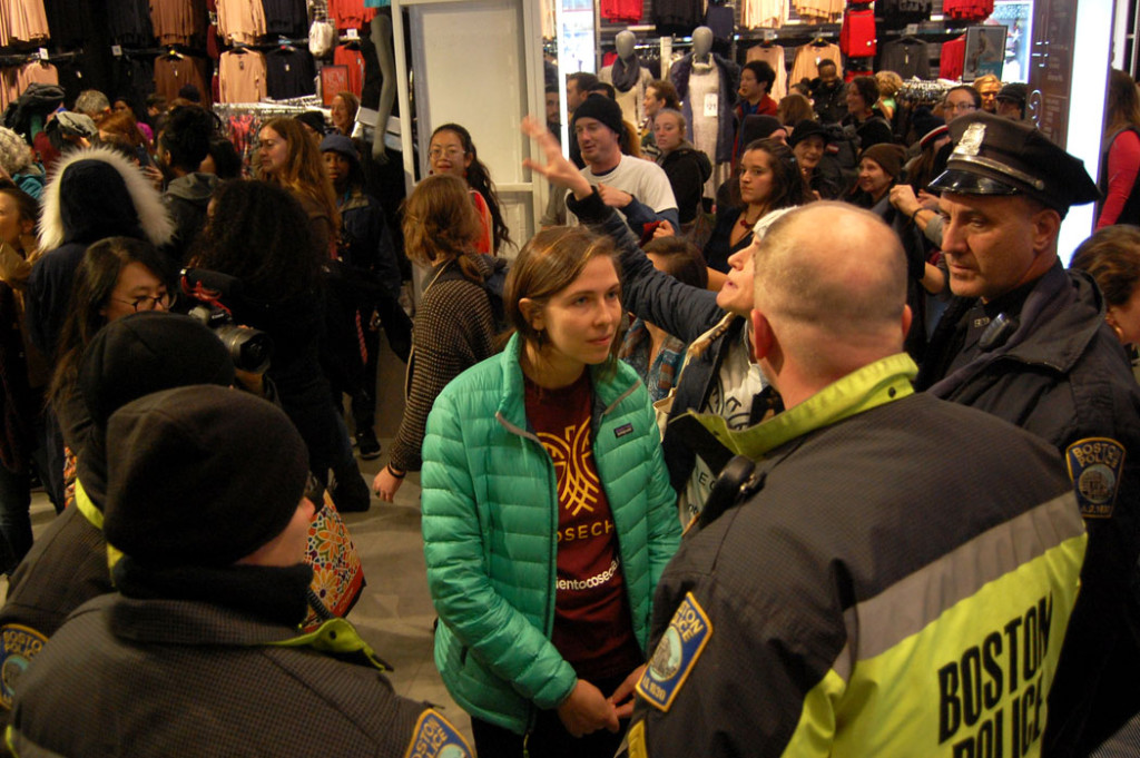 The protesters' police liaison speaks with Boston officers inside Primark. (Greg Cook)