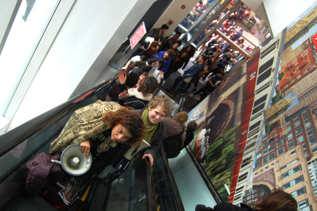 Immigrant rights advocates bring sound equipment up the escalator at T.J. Maxx. (Greg Cook)
