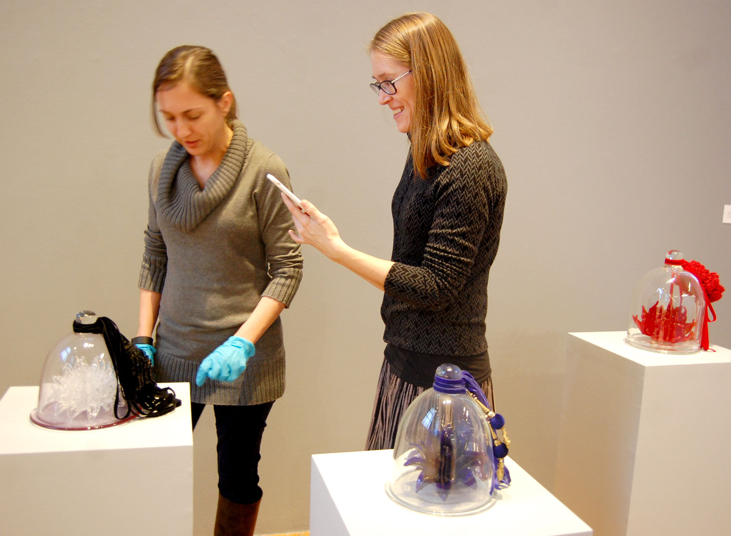 "At MassArt, Chloe Zaug Welch (left) and Darci Hanna carefully install glass sculptures by Petah Coyne in the Paine Gallery exhibit ""Vitreous Bodies: Assembled Visions in Glass."" Jan. 24, 2017. (Greg Cook)"
