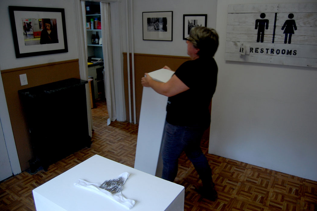 "Nave Gallery Director Susan Berstler moves a pedestal in a room featuring (from left) Lee Kilpatrick's photo of a woman with ""not my president"" written on face; Rebecca Schnopp's underwear with sharp pins; Russell DuPont's photo of a ""Dump trump"" protest sign leaning against park trash barrel; Chris D'Amore's photo of a protest; and Richard Ferrari's sign with movable parts so it says ""Restrooms"" or ""Arrestrooms."" (Greg Cook)"