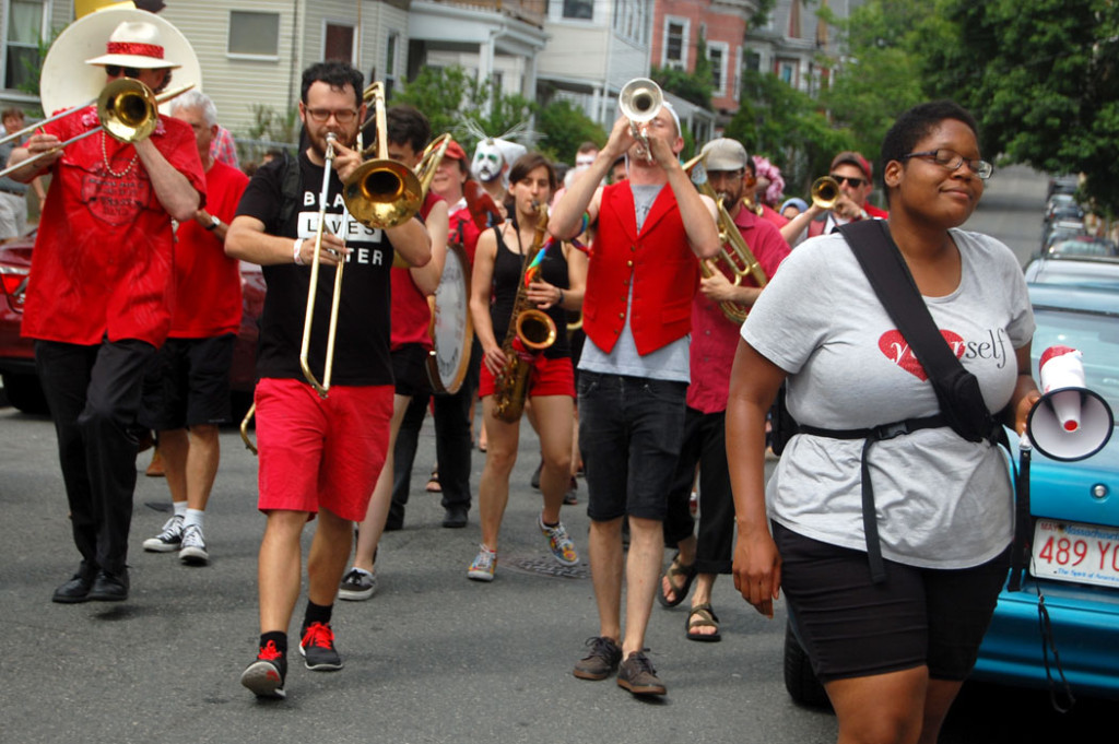 Deidra Montgomery, one of the festival organizers, walks with the Second Line Social Aid and Pleasure Society Brass Band during the festival's concluding parade. Second Line is a New Orleans-style street band based in Somerville and Cambridge that combines music with social action, performing at protests and peace rallies, as well as helping organize Somerville's annual Honk festival of activist street bands. (Greg Cook)