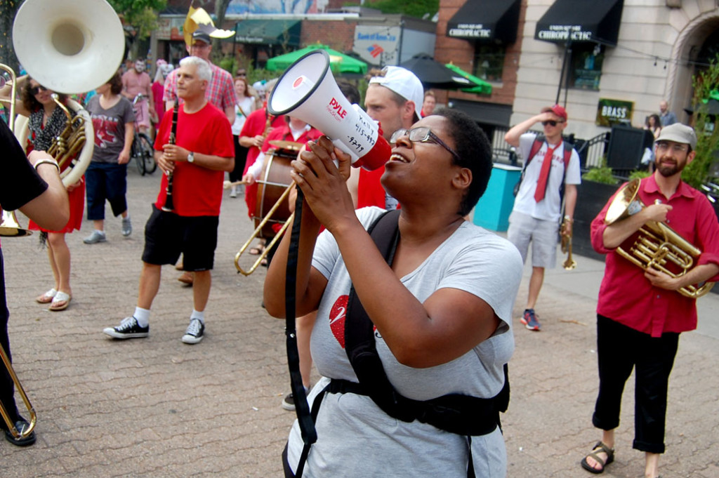 Deidra Montgomery, one of the festival organizers, leads chants during the festival's closing parade. (Greg Cook)