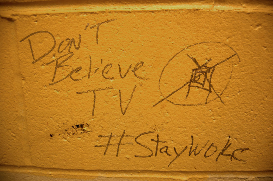 """Don't Believe TV #StayWoke"" graffiti in a bathroom at the MBTA's Oak Grove train station in Malden, Massachusetts, July 29, 2017. (Greg Cook)"