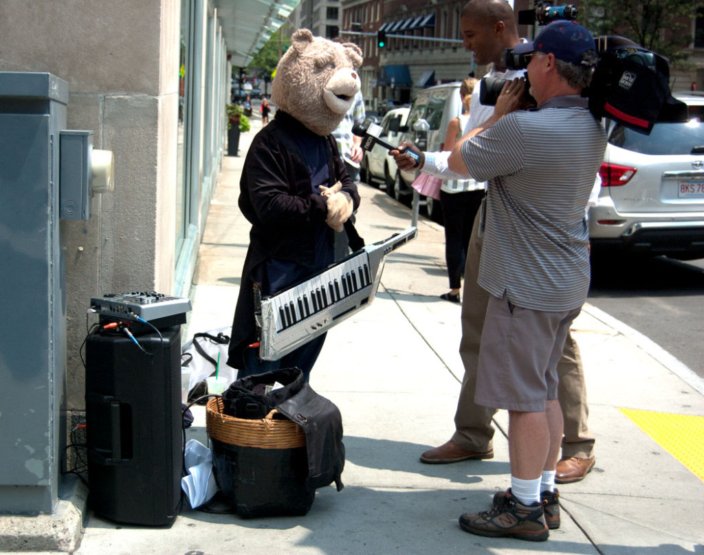 Keytar Bear gets interviewed by an NECN news crew on Stewart Street at Dartmouth Street in Boston, July 12, 2017. (Greg Cook)