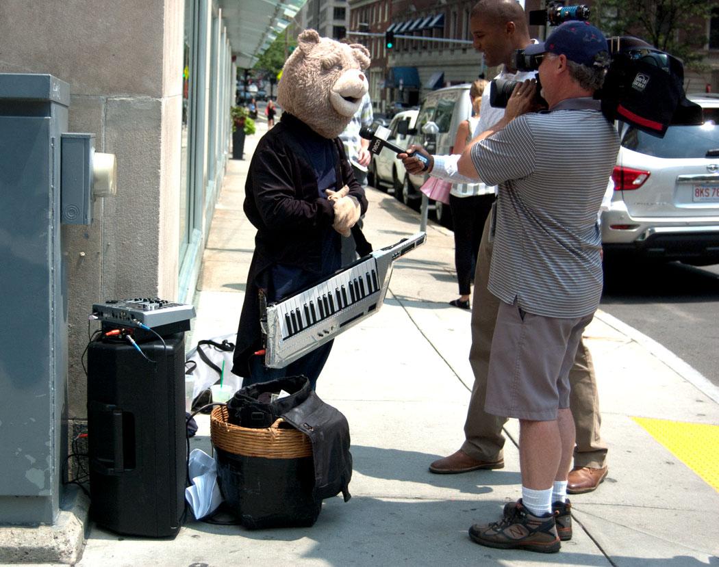 Keytar Bear gets interviewed by an NECN news crew on Stewart Street at Dartmouth Street in Boston, July 12, 2017. (Greg Cook)