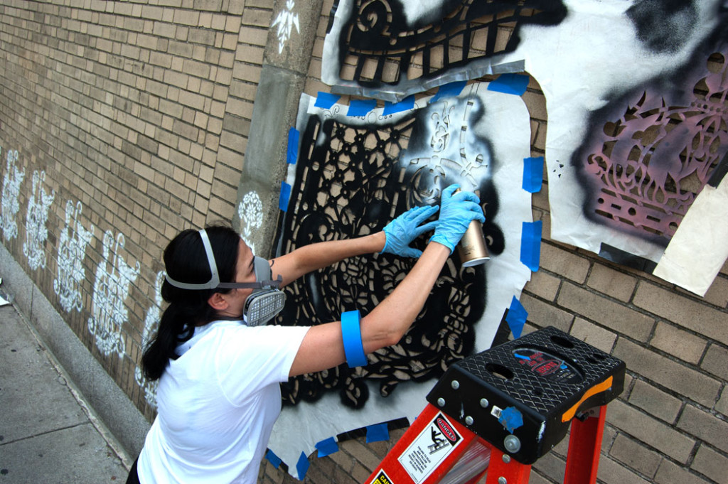 Vanessa Platacis (formerly known as PIXNIT) paints a mural on the 7-Eleven in Cambridge's Central Square, July 29, 2017. (Greg Cook)