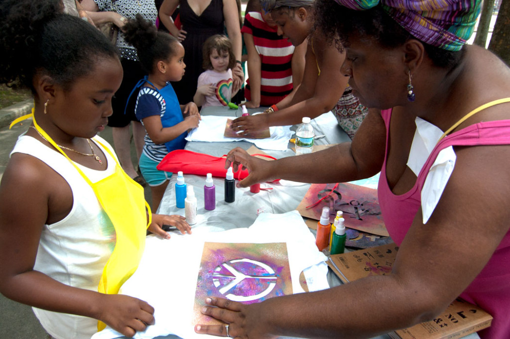 """Tanya Nixon-Silberg (right) of Wee The People helps kids stencil T-shirts at their """"Protestival"""" at Boston's Mozart Park, July 8, 2017. (Greg Cook)"""