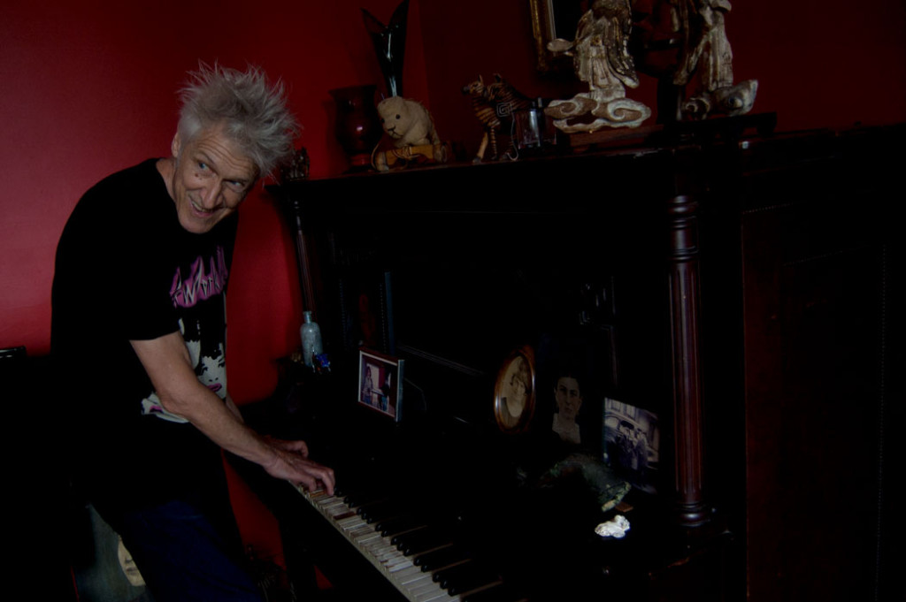 "Boston rock/punk legend Willie ""Loco"" Alexander plays piano in the living room of his Gloucester home, July 15, 2017. (Greg Cook)"