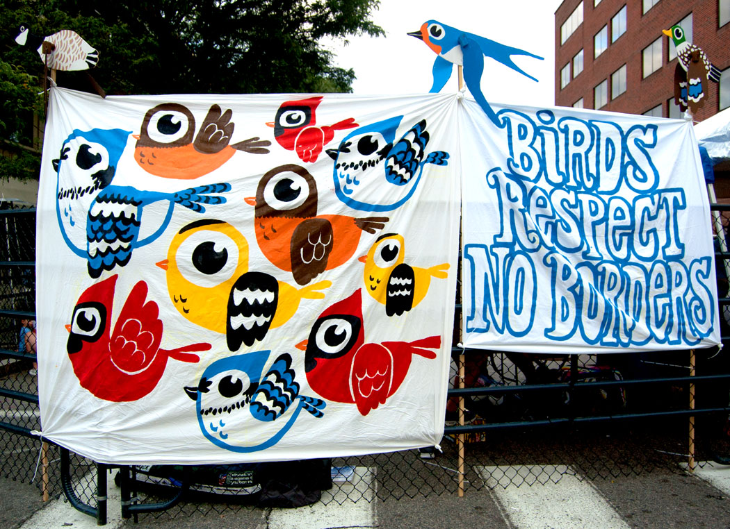 """""""Birds Respect No Borders"""" banners painted by Greg Cook on Foo Fest main gate. Whirligigs on top designed by Kari Percival and painted by Greg Cook (Greg Cook)"""