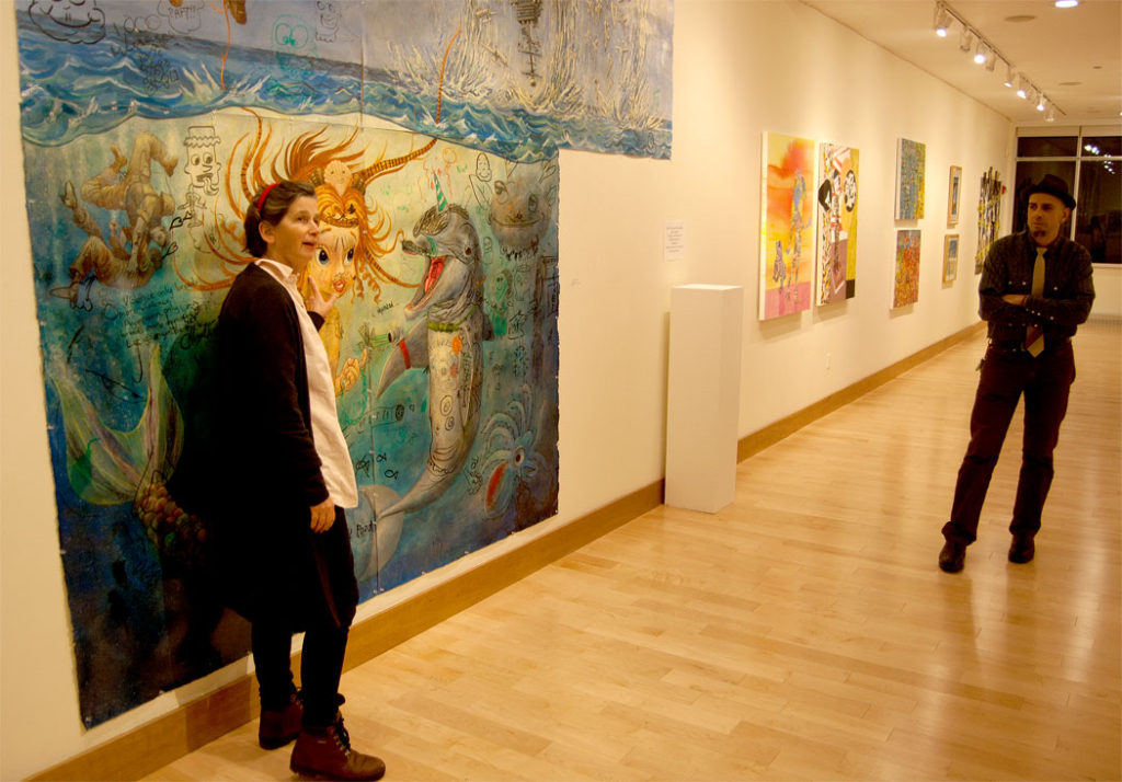 """Curator Elizabeth Keithline speaks about a painting by Edward Monovich (right) in """"Society in Upheaval"""" at Wheaton College. (Greg Cook)"""