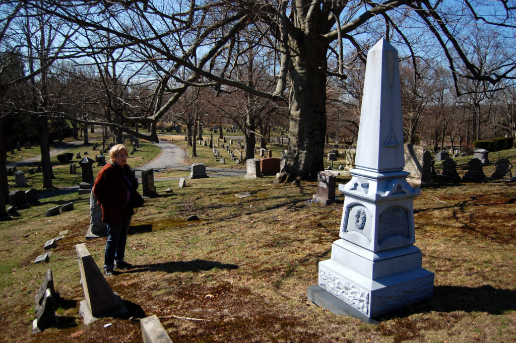 "Dee Morris, historian and city Cemetery Division trustee, looks at an obelisk in Medford's Oak Grove Cemetery for members of the Cook family who served in and survived the ""Mexican War,"" April 14, 2017. The monument was part of a late 19th century tombstone fad for monuments made to resemble granite, but that were are actually made from cast zinc sold as ""white bronze."" (Greg Cook)"