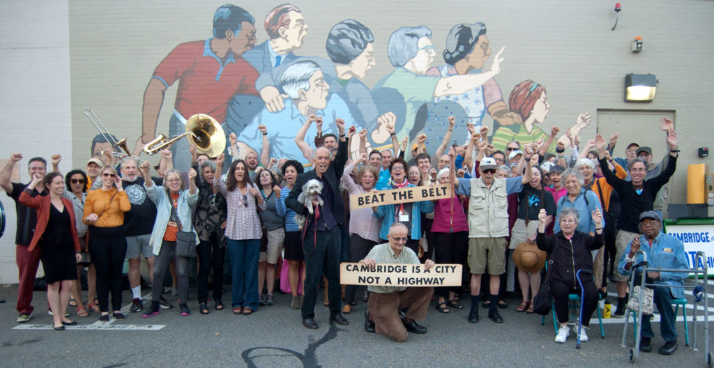 "Artist Bernard LaCasse (at center with dog) and friends celebrate the restoration by the Cambridge Arts Council of his 1980 mural ""Beat the Belt,"" behind 730 Memorial Drive in Cambridge, celebrating activists defeat of a planned highway that would have destroyed hundreds of buildings and displaced thousands of people in the city. Sept. 28, 2017. (Greg Cook/Cambridge Arts Council)"