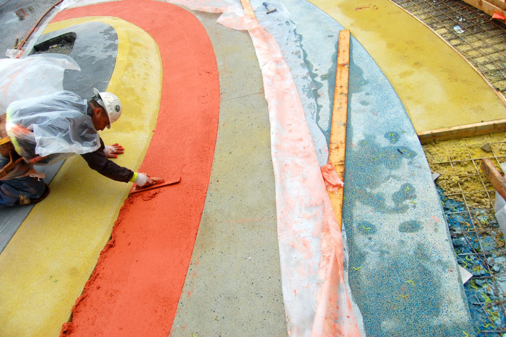 Smoothing concrete along the innovative public artwork by New York-based artists Chat Travieso and Yeju Choi that turns an everyday city sidewalk along Cambridge's Fern Street into a playful walking and biking path, May 26, 2017. (Greg Cook/Cambridge Arts Council)