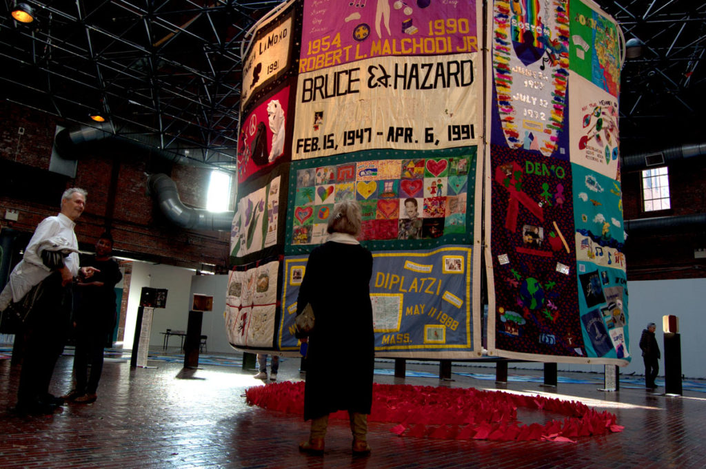 """Names Project AIDS Memorial Quilt panels hang suspended at the center of """"Medicine Wheel"""" at Boston Center for the Arts Cyclorama, Dec. 1, 2017. (Greg Cook)"""