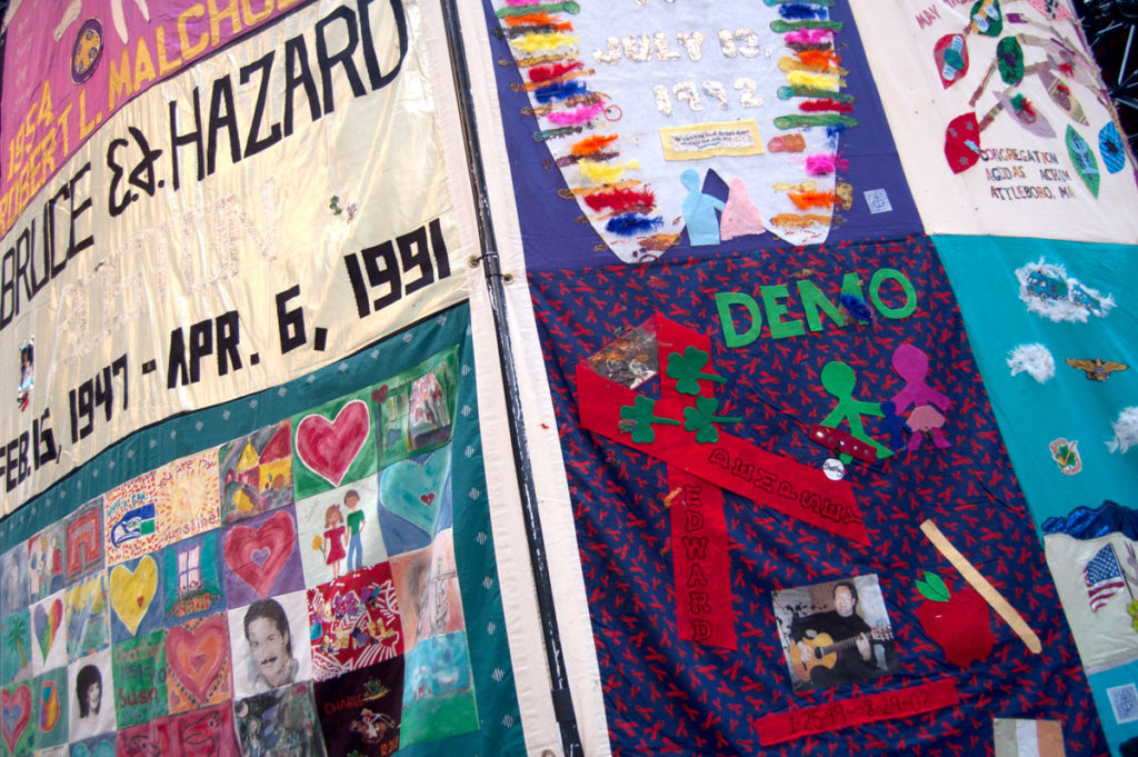 """Names Project AIDS Memorial Quilt panels suspended at the center of """"Medicine Wheel"""" at Boston Center for the Arts Cyclorama, Dec. 1, 2017. (Greg Cook)"""