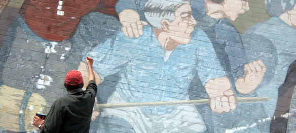 """Bernard LaCasse (pictured) works with conservators from the Cambridge Arts Council to restore his iconic """"Beat the Belt"""" mural in Cambridge, June 19, 2017. (Greg Cook)"""