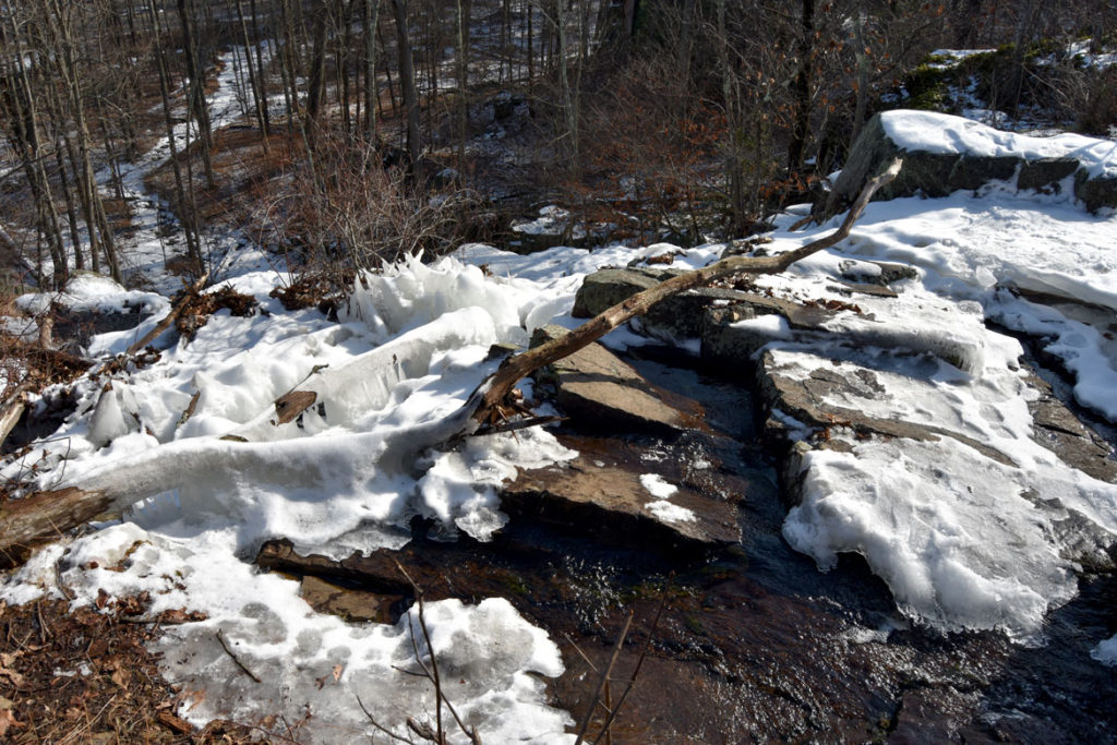 Atop the Cascade falls, looking over the edge as the brook runs toward Washington Street, in the Middlesex Fells, Melrose, Jan. 21, 2018. (Greg Cook)
