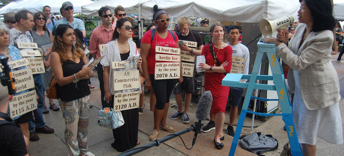 "Vivien Li, then president of The Boston Harbor Association, speaks outside the Boston Public Library in Copley Square at the beginning of the ""performative walk"" called ""Boston Coastline: Future Past"" that Andi Sutton and Catherine D'Ignazio led on June 19, 2015. (Greg Cook)"