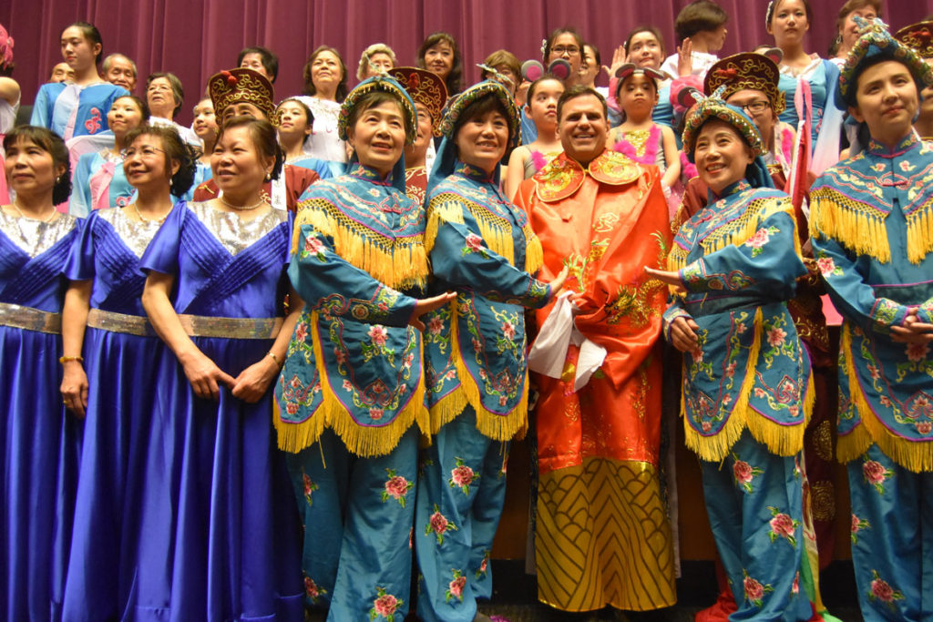 Performers pose with Malden Mayor Gary Christianson (front row, orange outfit) at Chinese Lunar New Year Celebration at Malden High School, Feb. 10, 2018. (Greg Cook)