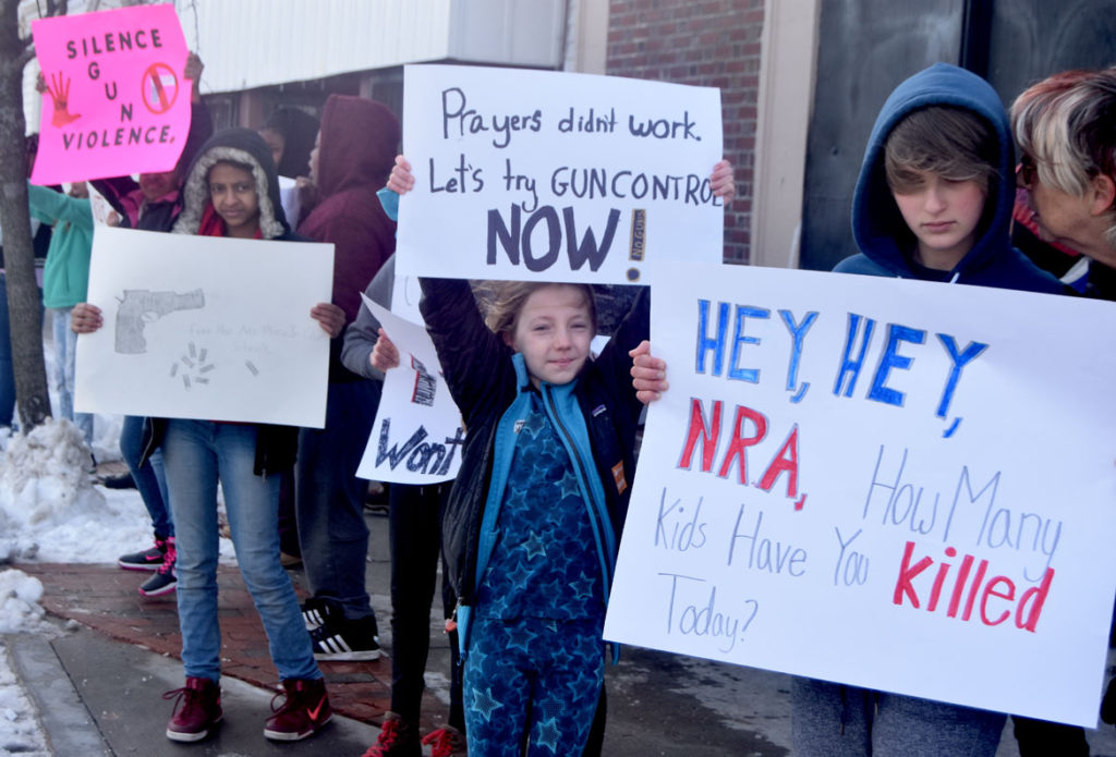 """Hey, Hey, NRA, How many kids have you killed today?"" Prayers didn't work. Let's try gun control now!"" Elementary students from Cambridgeport School protest guns on Broadway in Cambridge, March 15, 2018. (Greg Cook)"