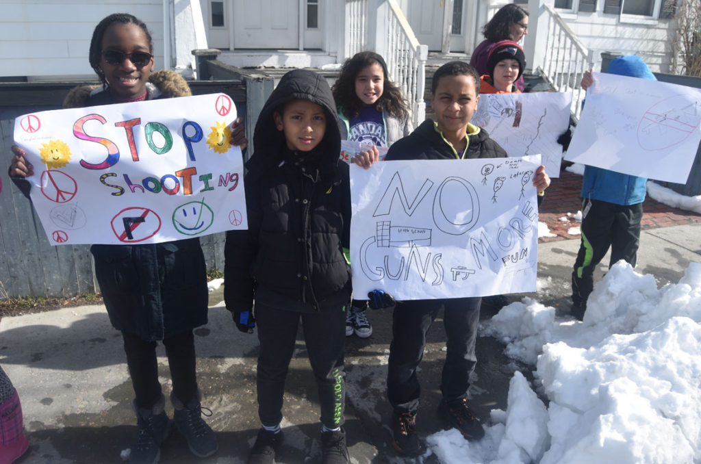 """Stop shooting."" Elementary students from Cambridgeport School protest guns on Broadway in Cambridge, March 15, 2018. (Greg Cook)"
