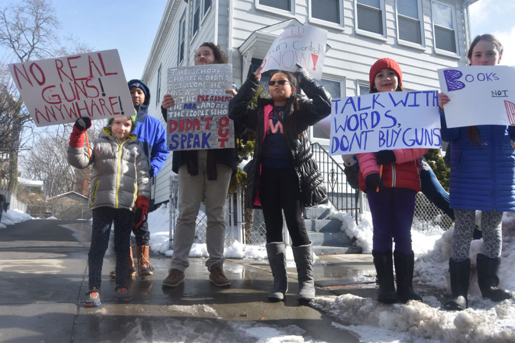 """No real guns! Anywhare!"" ""Talk with words, don't buy guns."" Elementary students from Cambridgeport School protest guns on Broadway in Cambridge, March 15, 2018. (Greg Cook)"
