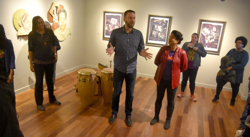 "Andrew Mroczek, associate director of exhibitions at Lesley University, introduces curator Dell M. Hamilton (in red coat) at the opening reception for ""SayHerName: Watch Us WERK"" at Lesley University College of Art and Design's VanDernoot Gallery in Cambridge, March 29, 2018. (Greg Cook)"