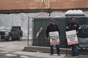 Carpenters union members protest a Nauset Construction retail and apartment project at 10 Essex St. in Cambridge's Central Square, April 13, 2018. (Greg Cook)