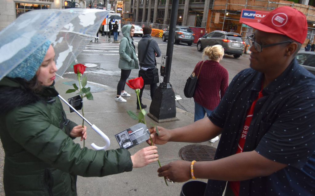 Cedric Douglas (right) handing out roses to remember more than 1,000 black people killed by police in the United States during the past five years. April 27, 2018. (Greg Cook)