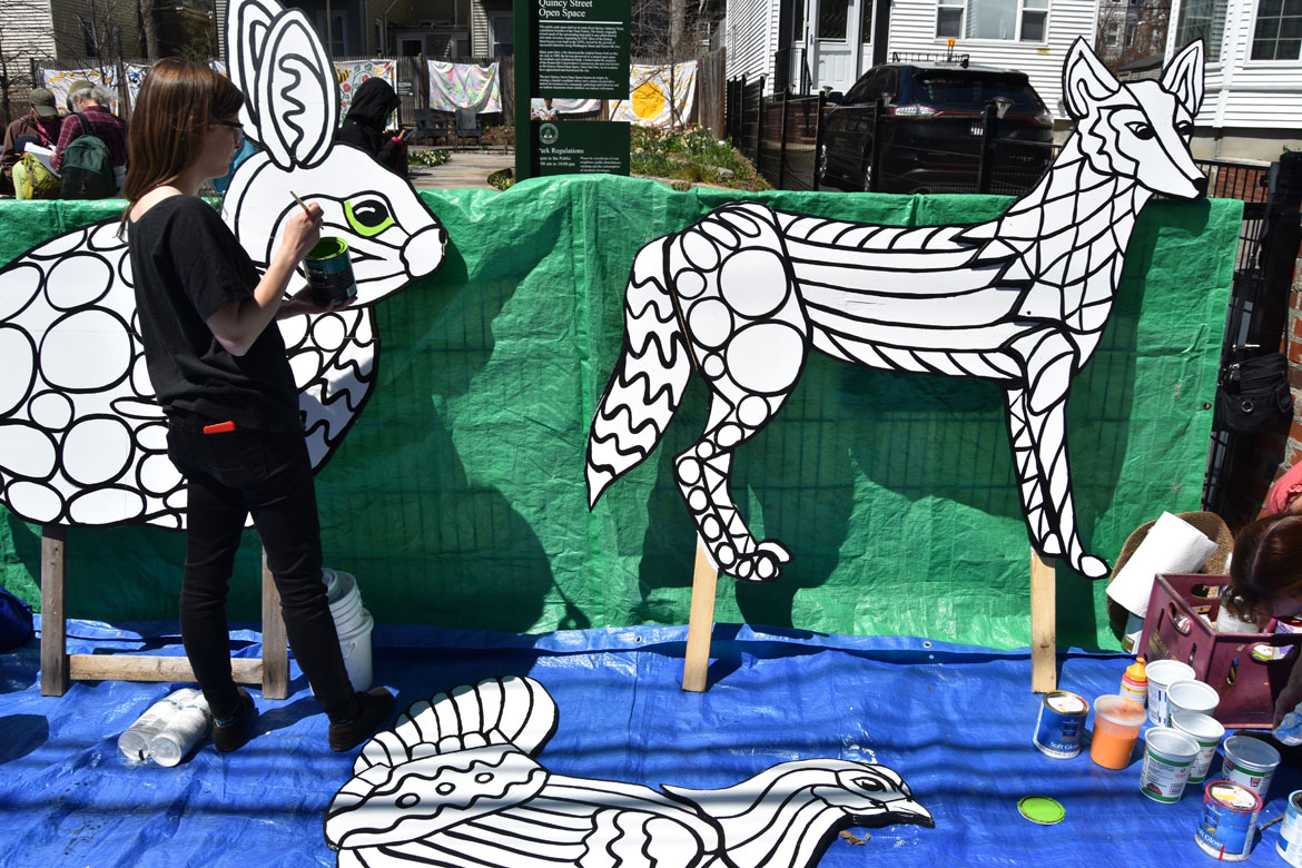 Festival co-organizer Nina Eichner helps paint mosaic-style animals designed by muralist Liz LaManche at the Starting Over Festival, Somerville, April 22, 2018. (Greg Cook)