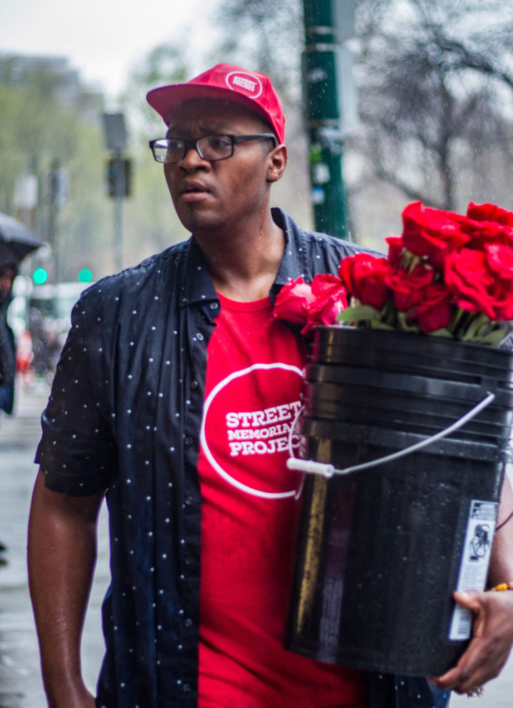 Cedric Douglas hands out roses to remember more than 1,000 black people killed by police in the United States the past five years. April 27, 2018. (Photo by Hannah Bailey)