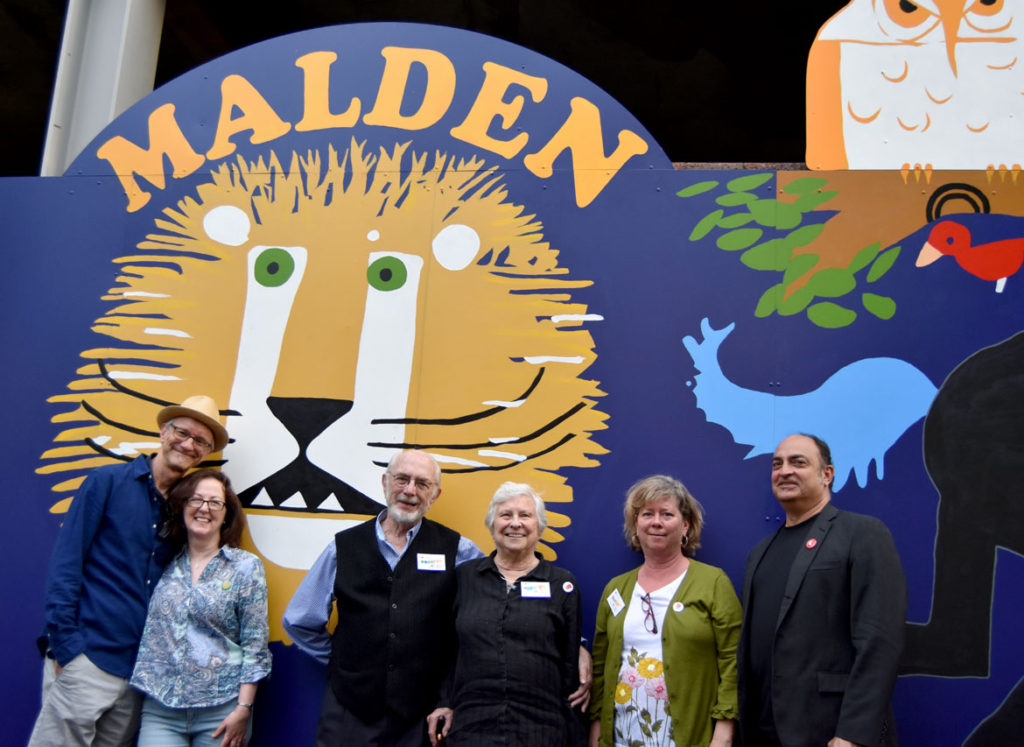 "The Emberley family of illustrators. From left, son Michael Emberley and his wife Marie-Louise Fitzpatrick, Ed and Barbara Emberley, daughter Rebecca Emberley and her husband, musician Peter Black at ""The Wonderful World of Ed Emberley"" mural on Exchange Street, Malden, May 23, 2018. (Greg Cook)"