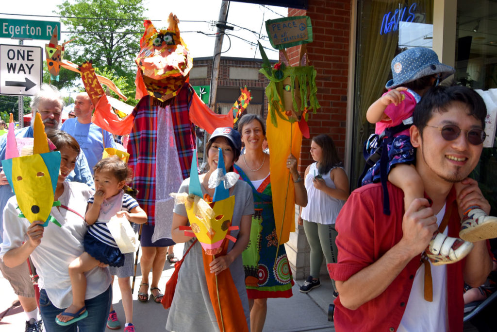 Fox masks and one of the giant fox puppets, created under the leadership of Sara Peattie of the Boston Puppeteers Cooperative, at the Fox Festival Parade in Arlington, June 16, 2018. (Greg Cook)