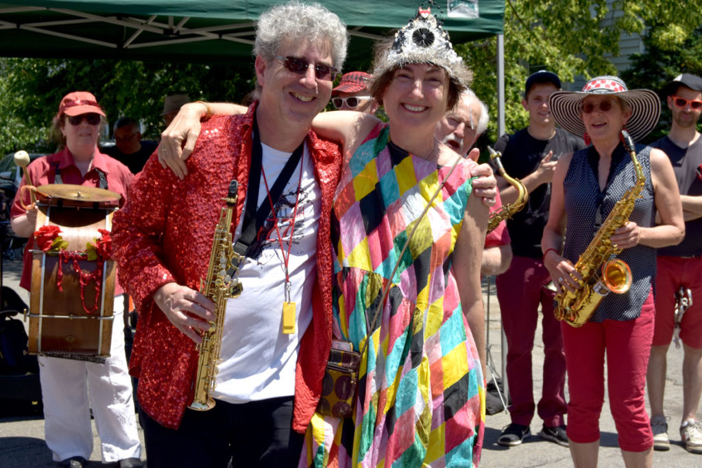 Ken Field (left) of the Second Line Social Aid & Pleasure Society Brass Band with parade organizer, Cecily Miller of Arlington Public Art, at the Fox Festival Parade in Arlington, June 16, 2018. (Greg Cook)