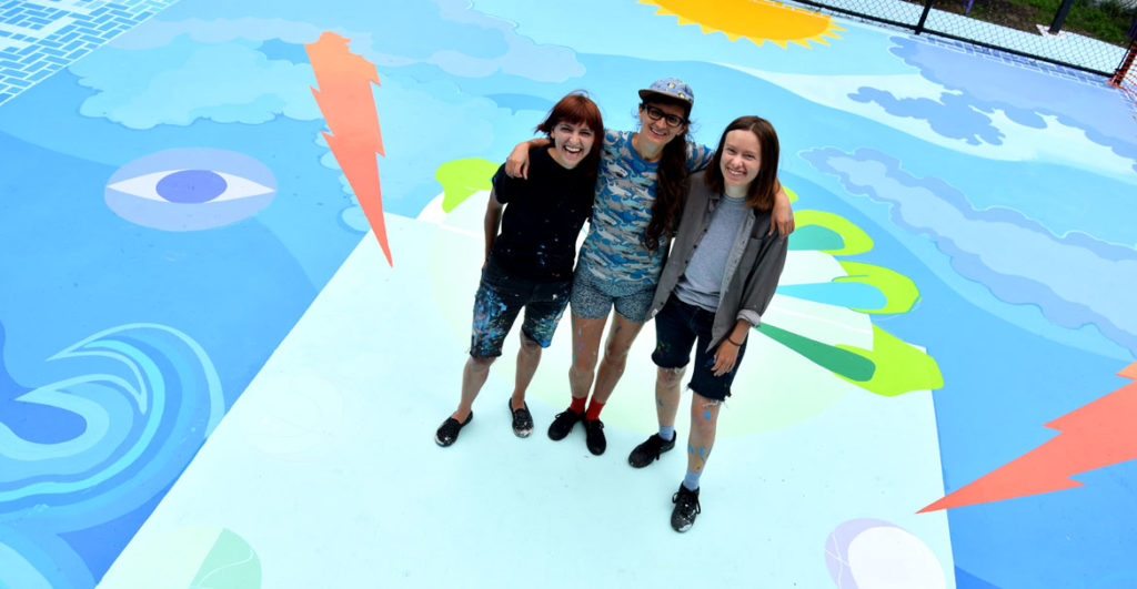 "Kristine Roan (from left), Maria Molteni and Jena Tegeler at the ""Storming the Court"" mural (in progress) in Salem, June 13, 2018. (Greg Cook)"