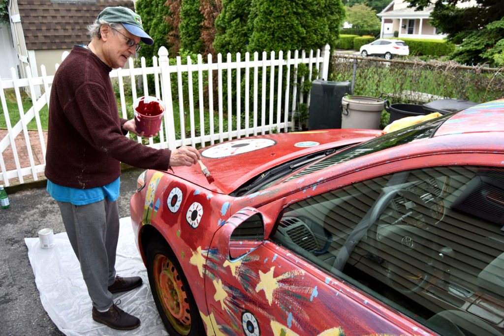 Mark Alston-Follansbee painting his art car in the driveway of his Waltham home, May 28, 2018. (Greg Cook)