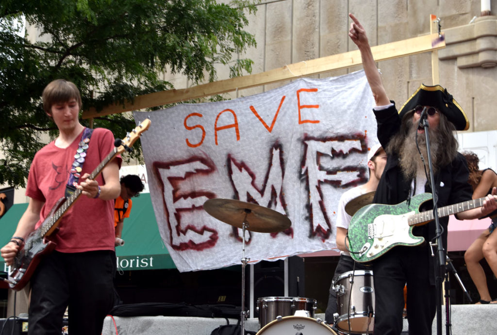 "Jonee Earthquake Band plays at the ""Save EMF"" rally in Harvard Square, Cambridge, June 16, 2018. (Greg Cook)"