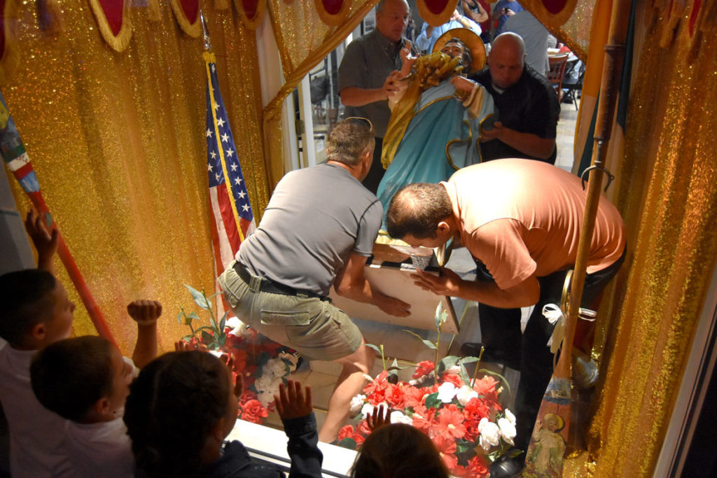 Returning the statue of St. Peter to the window shrine of the St. Peter's Club on Rogers Street at the end of the Novena (nine days of prayer) that serve as a prelude to the St. Peter's Fiesta, June 26, 2018. (Greg Cook)