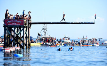 To win the Greasy Pole contest, walkers must make it to the end of a grease-slathered telephone pole to grab a flag off the end, June 29, 2018. (Greg Cook)