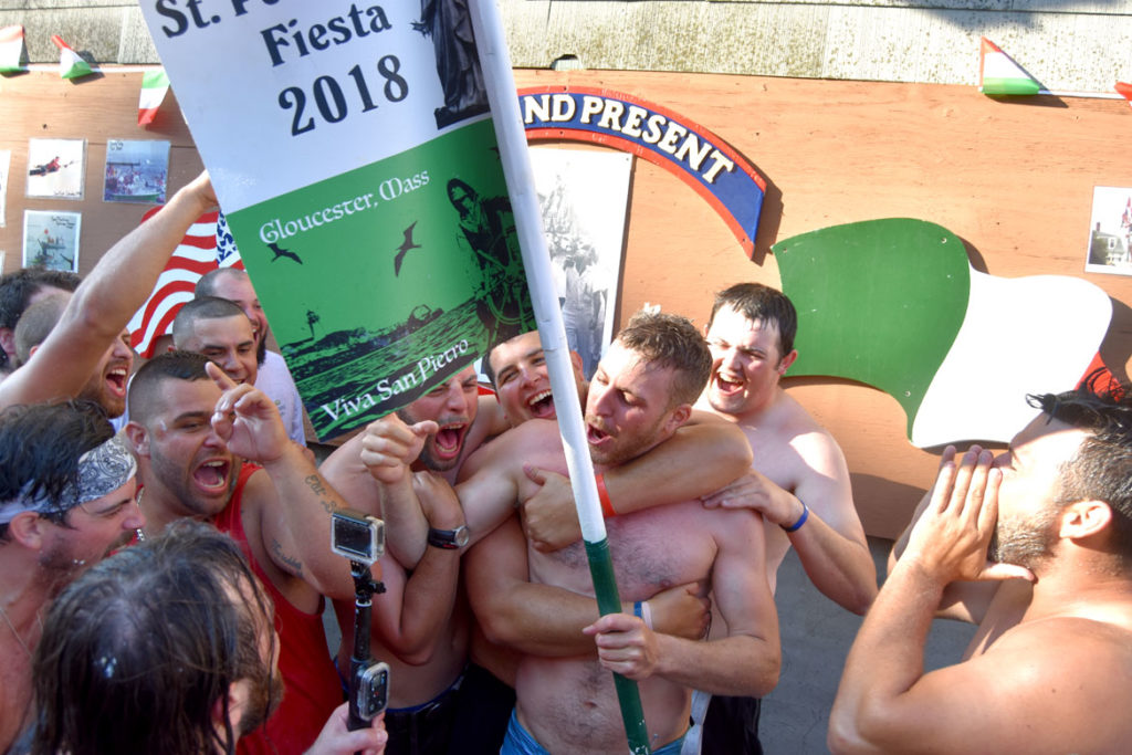 Frank Taormina (center) celebrates with fellow Greasy Pole walkers at the shrine on Commercial Street after winning the contest, June 29, 2018. (Greg Cook)