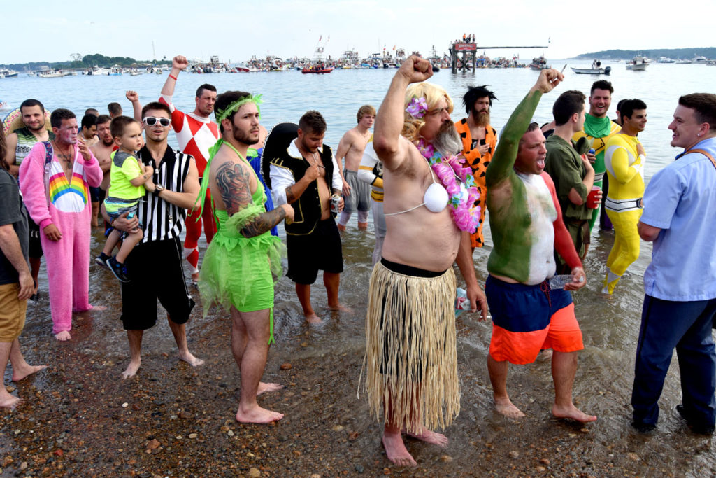 Costumed Greasy Pole contestants wait on Pavilion Beach to be ferried out to the platform (in the distance) for the contest, June 30, 2018. (Greg Cook)