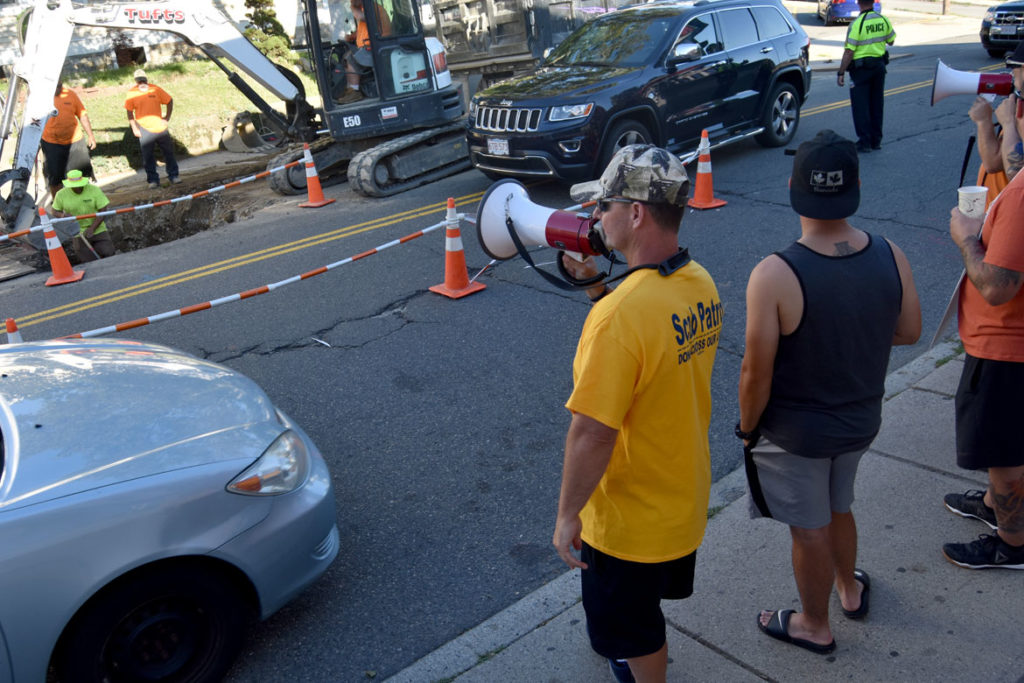 """""""Scab Patrol: Do Not Cross Our Line,"""" reads the T-shirt. Gas workers, locked-out by National Grid in a contract dispute, protested at a company work site on Main Street in Malden, July 19, 2018. (Greg Cook)"""
